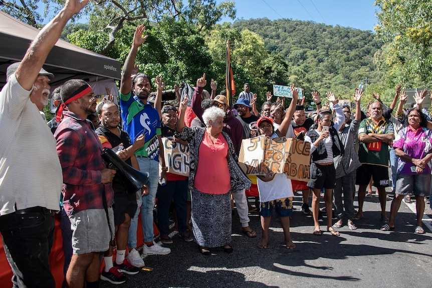 A group of colourfully dressed Indigenous protesters gathered at a police checkpoint.