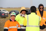 Four people in hi-vis vests stand, one with his back to the camera.