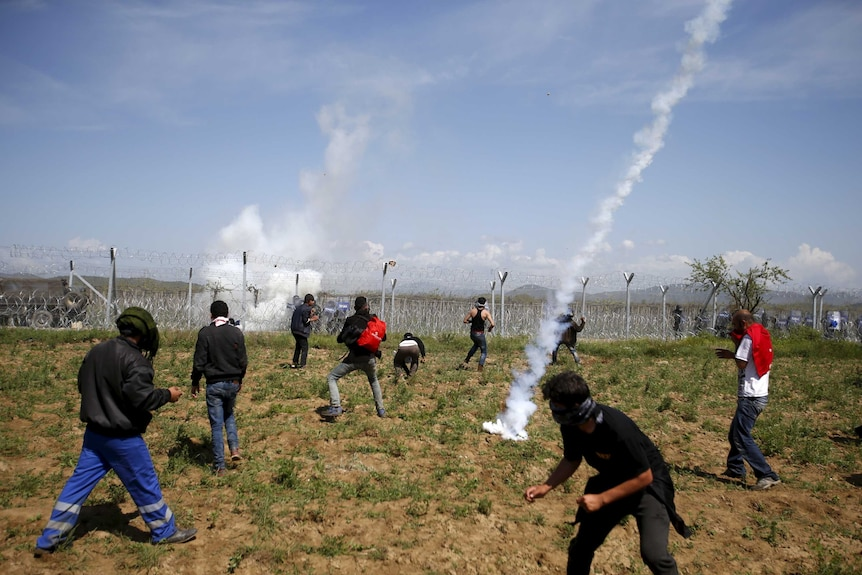 A teargas canister thrown by Macedonian police lands among protesting asylum seekers.
