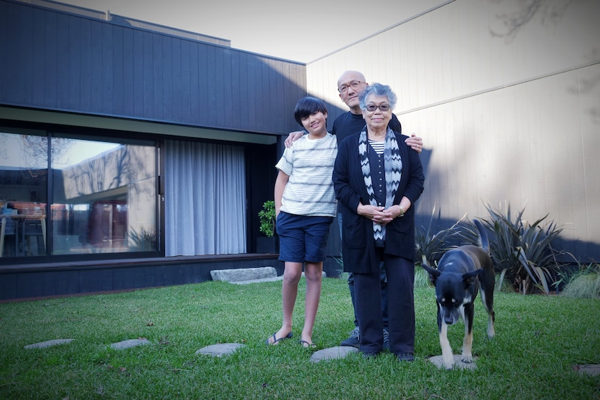 Three family members stand in front of their house