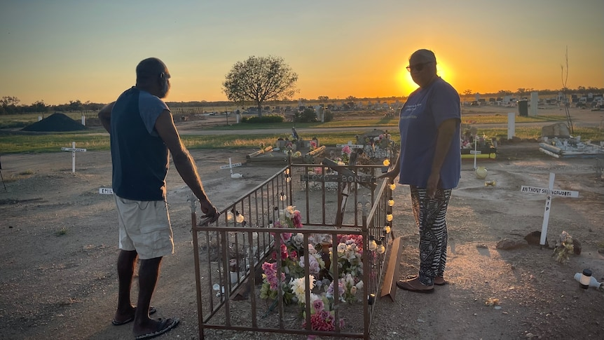 Two people stand on either side of a grave, it has a knee-high wrought iron fence and flowers.