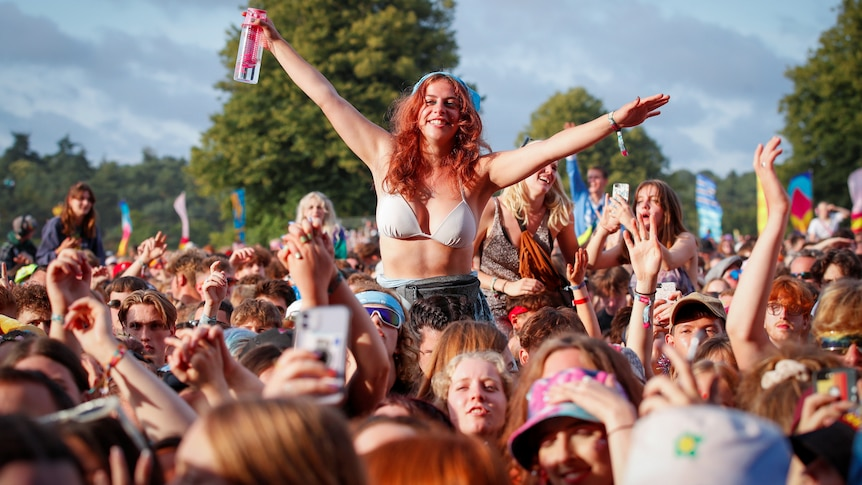 A girl sitting on someone's shoulders outstretches her arms and grins at a packed outdoor mosh pit