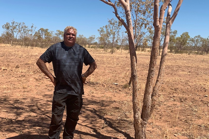 An Indigenous man with grey hair stands in sparse bushland with his hands on his hips.
