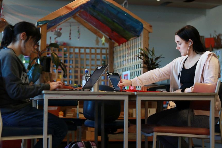 Two young women do schoolwork on laptops with a classroom nursery in background