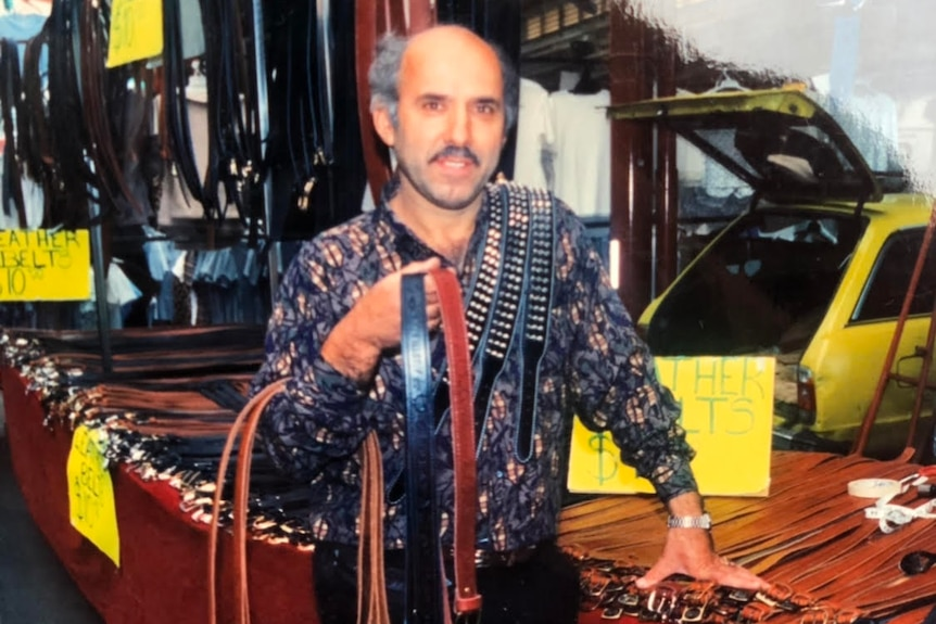 A man holds leather belts at a market stall in the 1980s