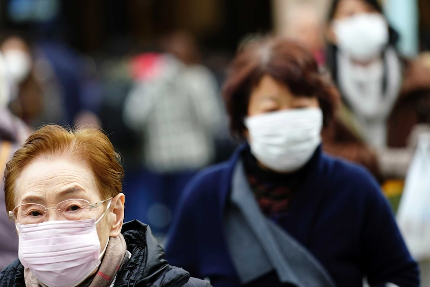 An elderly lady with glasses and another woman can be seen wearing masks.