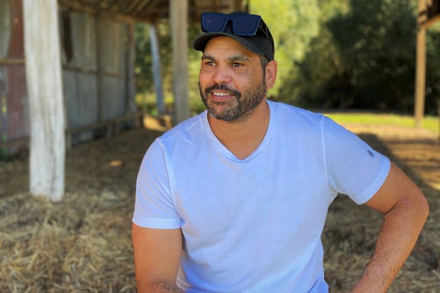 Greg Inglis smiles wearing a baseball cap and hoodie