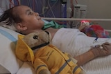 A photo of Kye Ryan lying in a hospital bed in Perth with a teddy next to him