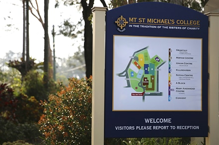 Welcome sign outside Mt St Michael's College next to a hedge.
