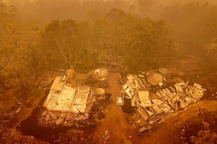 An aerial view of a building burnt to the ground surrounded by bushland and an orange low in the sky
