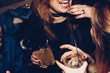 Two women hold drinks and laugh.