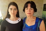 Two women stare ahead and do not smile