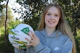 A teenage girl smiles as she holds a netball.
