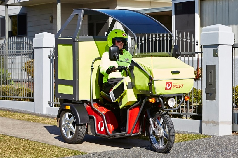 A postie clad in fluoro yellow clothes rides a motorised three wheeled motorbike which has a sunshade over the top.