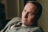 Colour still of Christian Bale looking solemn while seated in front of microphone and his hand on a gavel in 2018 film Vice.