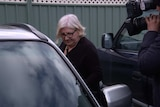 A woman gets into a car as a television camera records her.
