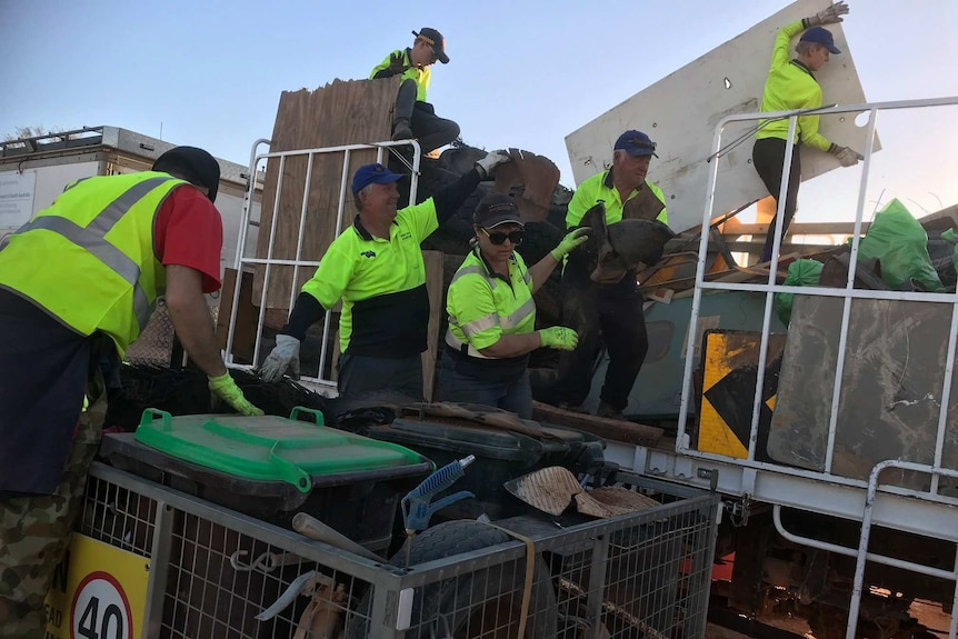 Six volunteers wearing caps and green high-visibility shirts put rubbish into a trailer.
