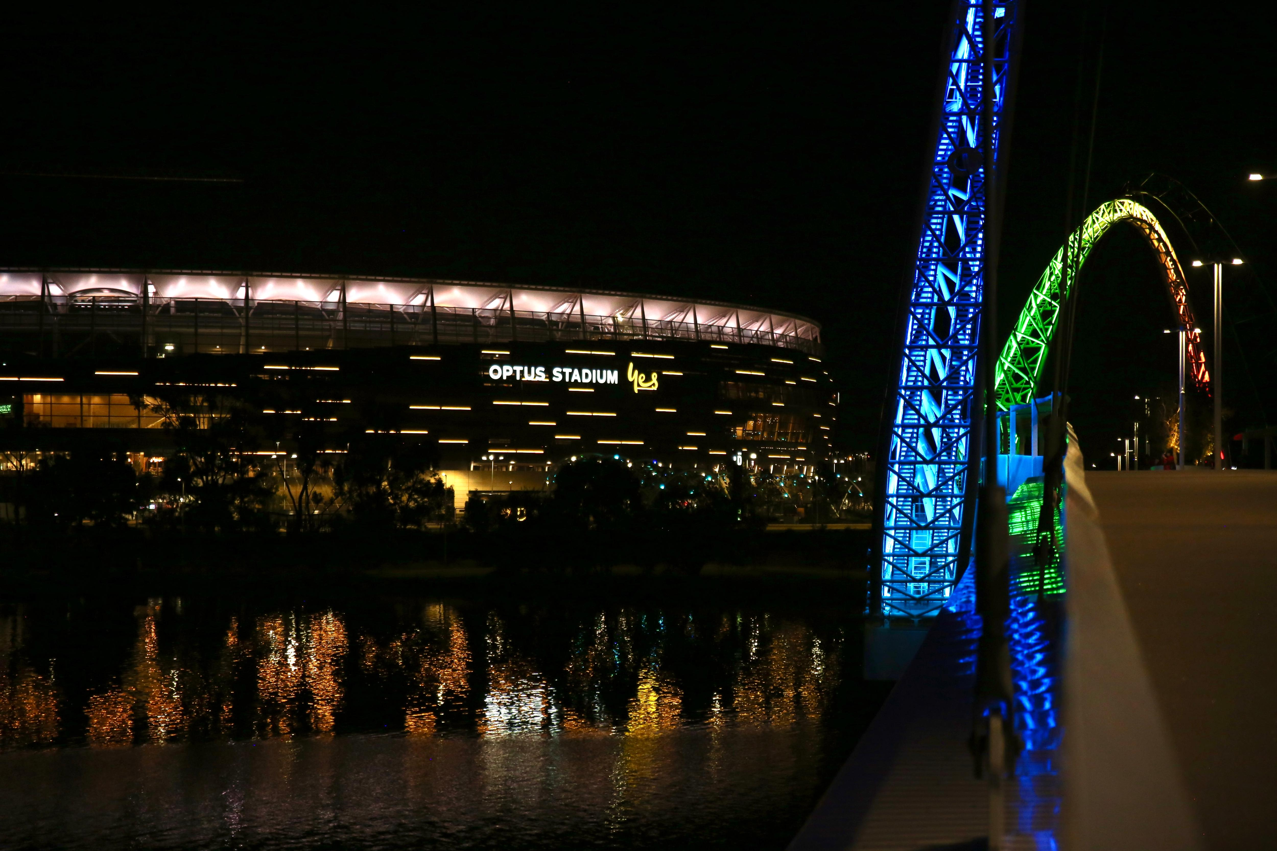Perth Stadium at night reflecting onto the river as seen from Matagarup Bridge lit up blue and green