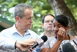 Nova Peris wipes a tear from her eye as she stands in front of microphones