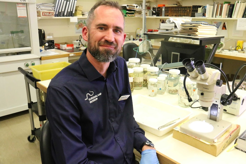 Dr Andrew Amey sits in a lab, smiling