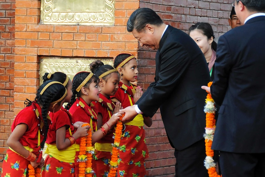 Chinese President Xi Jinping is greeted by Nepalese children upon arrival in Kathmandu