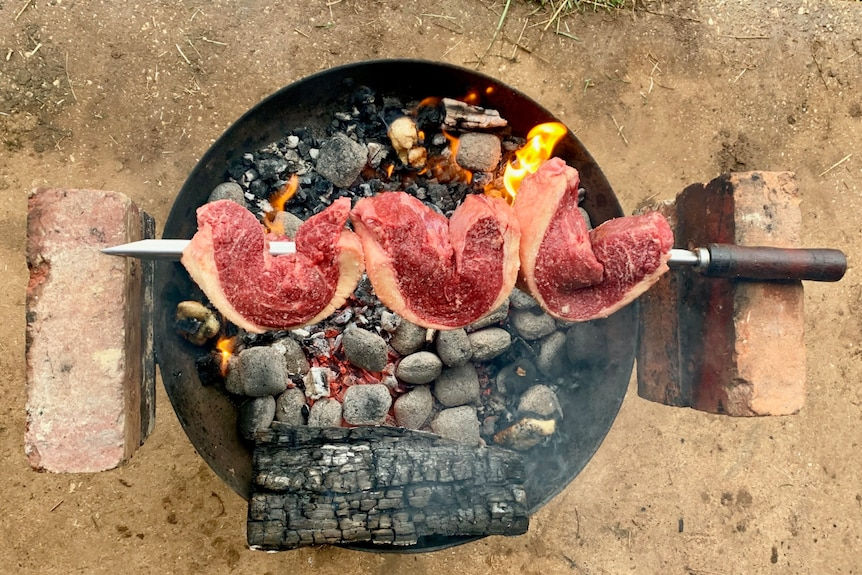 Cuts of meat skewered on a sword cook over a bucket of hot coals