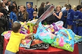 A pile of showbags tempts a young boy who reaches across and grabs what he wants in Perth