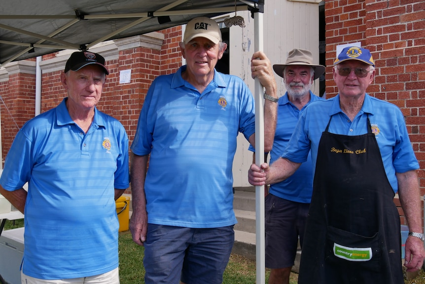 Four men aged in their 70s and 80s near a BBQ.