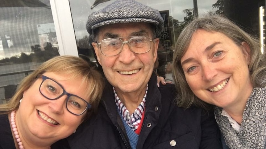 A man with his two adult daughters, all smiling.