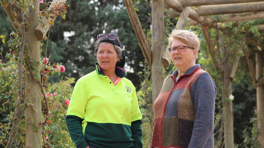 a woman wearing a hi-vis shirt speaks with another woman in a rose garden in a wooden walkway