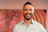An Aboriginal man with short hair, beard and white shirt standing in front a colourful Aboriginal dot painting