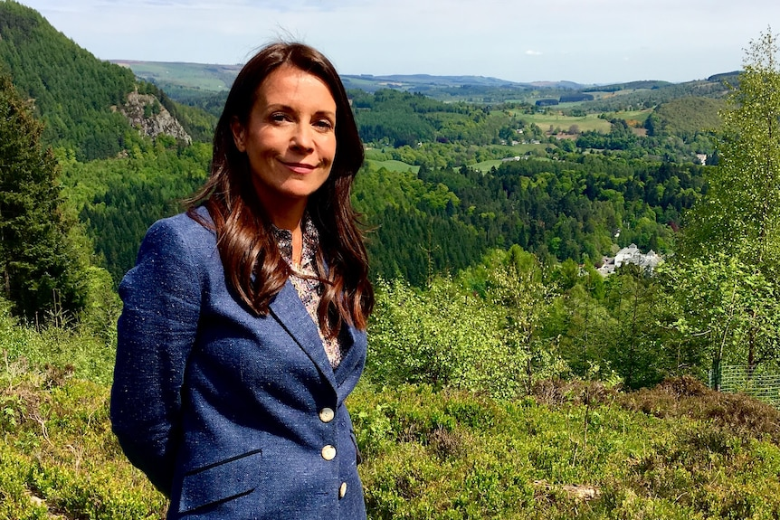 A woman in her early 40s with long brown hair and wearing a blue blazer stands in lush green countryside