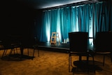 An empty room with a lit up blue curtain and stage with a vacated stool