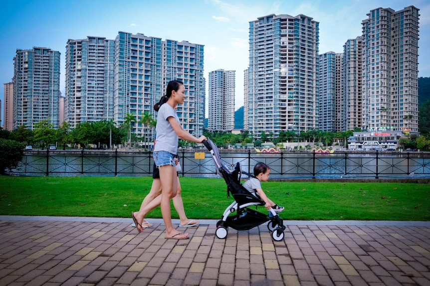 A woman pushes a baby in a pram past a row of high rise residential buildings