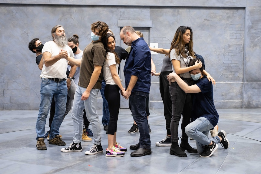 A cast of people of different ages and backgrounds, some positioned as if dancing, or back to back, or holding hands, or hugging