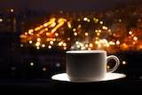 A cup of coffee in a window against the background of city lights
