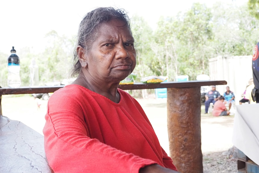 An older Indigenous woman in bright clothes sitting outside.