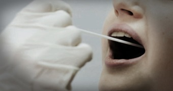 A gloved hand places a swap on an open mouth
