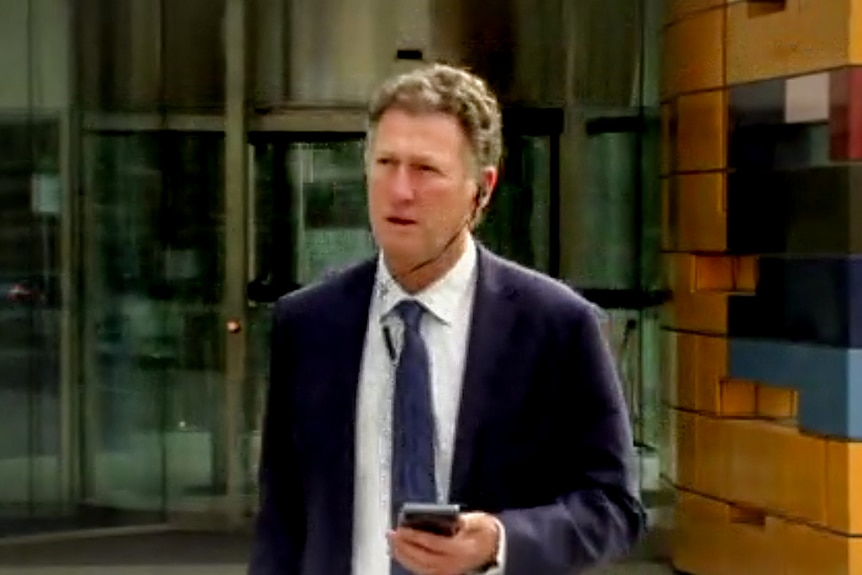 Johnathan Kenny, wearing a suit and tie with headphones in, leaves the orange Federal Court building.