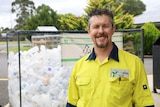 """A man wearing a high vis shirt reading """"Ecoplas"""" smiles in front of a big container of empty plastic milk bottles."""