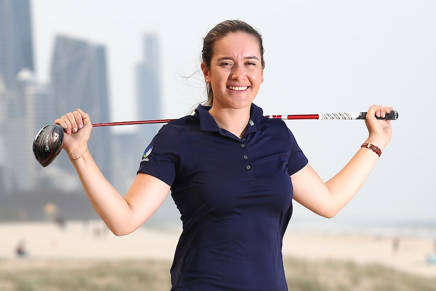 A woman in golf attire holds her club behind her shoulders and smiles for the camera.