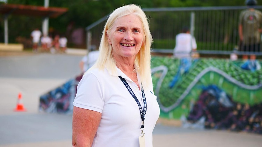Woman in a white shirt with a lanyard and white hair standing in front of a skateboard park.