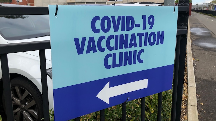 A sign on a fence saying COVID–19 vaccination clinic with an arrow to the left