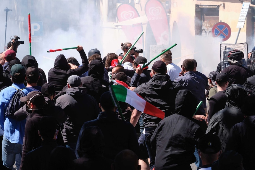 A crowd wave batons as an Italian flag can be seen above the crowd.