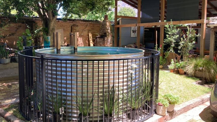 A large steel tank filled with water and a small ladder sits in a garden.
