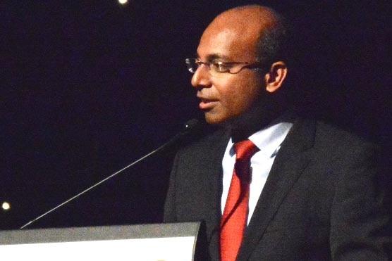 Adani CEO Jeyakumar Janakaraj speaks at a podium.