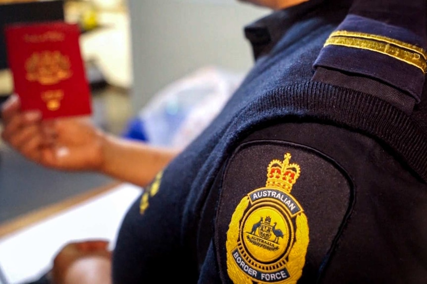 An Australian Border Force officer, with badge in foreground, holds a passport in background.