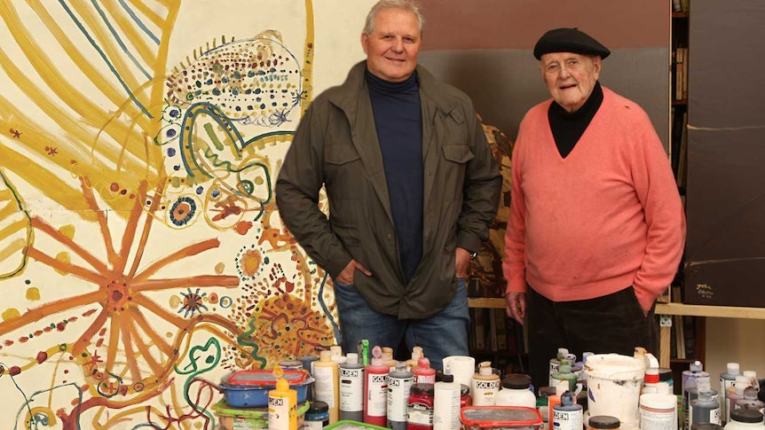 An elderly man and his adults son stand in an art studio in front of canvas