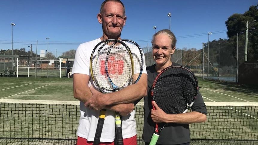 A man smiles holding a tennis racquet on a court next to a woman holding a racquet