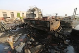A damaged tugboat covered in black marks like from fire or dirt, sits on a pile of bent amid debris and wreckage next to water